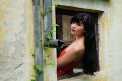 Belle jeune femme de brune dans la fenêtre image stock