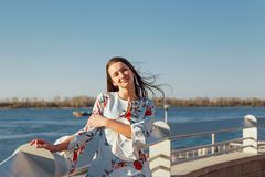 Belle jeune femme de brune dans la robe bleue appréciant le lever de soleil par la mer image libre de droits