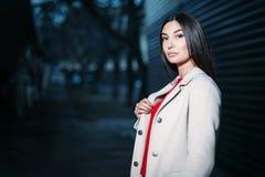Belle jeune femme de brune dans le manteau blanc de chemisier rouge égalisant dehors Copiez l'espace image libre de droits