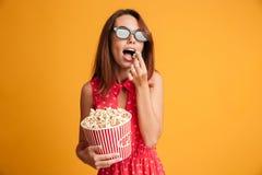 Belle jeune femme de brune dans les verres 3d et l'eatin rouge de robe Photo libre de droits