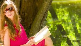 Belle jeune femme de brune lisant un livre clips vidéos