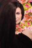 Belle jeune femme de brune sur un fond floral rose Photos stock