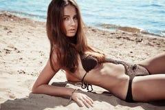 Belle jeune femme de brune sur une plage ensoleillée images libres de droits