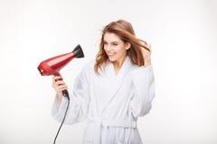 Belle jeune femme de Cheeful séchant ses cheveux avec le dessiccateur photo stock