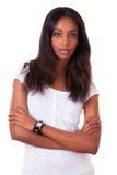 Belle jeune femme de couleur avec les bras pliés image stock