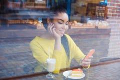 Belle jeune femme de métis vue par la fenêtre de la boulangerie photos stock