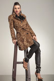 Belle jeune femme de mode s'asseyant sur un tabouret Photo stock