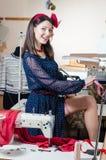 Belle jeune femme de pin-up drôle sexy avec la machine à coudre et la jambe de mesure avec l'appareil-photo de sourire de bande e Images libres de droits