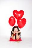 Belle jeune femme de Saint-Valentin portant la robe rouge et tenant les ballons rouges photo stock