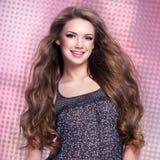Belle jeune femme de sourire avec de longs poils regardant l'appareil-photo Photos stock