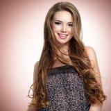 Belle jeune femme de sourire avec de longs poils regardant l'appareil-photo image libre de droits