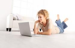 Belle jeune femme de sourire avec l'ordinateur portable d'ordinateur, se trouvant sur le liv photographie stock
