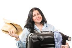 Belle jeune femme de sourire de brune avec le chapeau dans sa main et valise d'isolement sur le fond blanc Concept de tourisme photos libres de droits