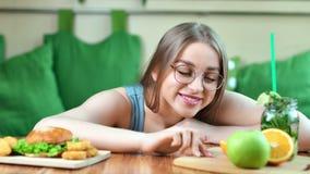 Belle jeune femme de sourire en gros plan moyenne choisissant entre le fruit frais et le gros hamburger clips vidéos