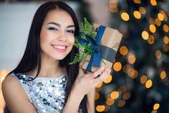 Belle jeune femme de sourire enthousiaste avec le cadeau actuel sentant l'arbre de Noël proche heureux Portrait en gros plan Photos libres de droits