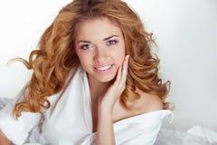 Belle jeune femme de sourire heureuse avec les cheveux bouclés dans le lit à ho Photos stock