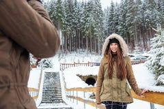 Belle jeune femme de sourire se tenant et posant dans la forêt d'hiver Photographie stock libre de droits