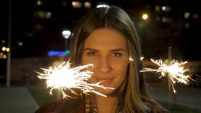 Belle jeune femme de sourire tenant un cierge magique Scène de nuit Jeune fille de sourire tenant le cierge magique dans sa main  image stock
