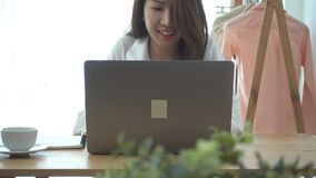 Belle jeune femme de sourire travaillant sur l'ordinateur portable tout en appréciant buvant du café chaud se reposant dans un sa banque de vidéos