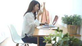 Belle jeune femme de sourire travaillant sur l'ordinateur portable tout en appréciant buvant du café chaud se reposant dans un sa clips vidéos