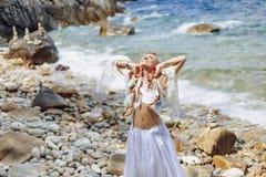 Belle jeune femme de style de boho dans la robe blanche sur la plage en pierre Photos libres de droits