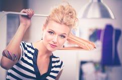 Belle jeune femme de styliste près de support avec des cintres Photographie stock