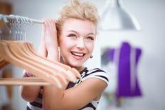 Belle jeune femme de styliste près de support avec des cintres Photo libre de droits