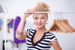 Belle jeune femme de styliste près de support avec des cintres Images stock
