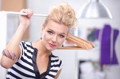 Belle jeune femme de styliste près de support avec des cintres Image stock