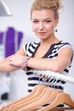 Belle jeune femme de styliste près de support avec des cintres Photo stock