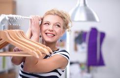 Belle jeune femme de styliste près de support avec des cintres Image libre de droits