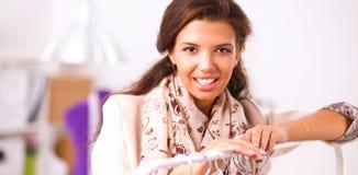 Belle jeune femme de styliste près de support avec des cintres Images libres de droits