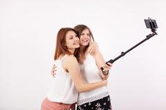 Belle jeune femme deux prenant un selfie avec un bâton de selfie Image libre de droits