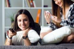 Belle jeune femme deux restant sur le sofa à la maison Images libres de droits
