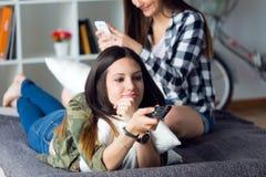 Belle jeune femme deux restant sur le sofa à la maison Image stock