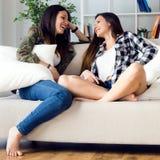 Belle jeune femme deux restant sur le sofa à la maison Image libre de droits