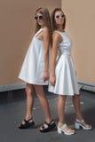 Belle jeune femme deux sexy dans la robe blanche à la mode posant sur un toit avec des lunettes de soleil pendant le jour d'été l Images libres de droits