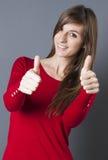 Belle jeune femme discrète souriant avec des pouces  Image stock