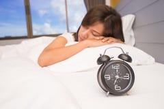 Belle jeune femme dormant et souriant tout en se situant dans le lit confortablement et avec bonheur sur le fond du réveil images stock