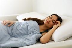 Belle jeune femme dormant tout en se situant dans le lit confortablement et avec bonheur photo libre de droits