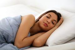 Belle jeune femme dormant tout en se situant dans le lit confortablement et avec bonheur images stock