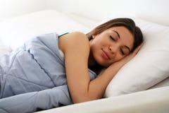 Belle jeune femme dormant tout en se situant dans le lit confortablement et avec bonheur photographie stock libre de droits