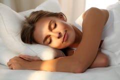 Belle jeune femme dormant tout en se situant dans le lit confortablement et avec bonheur Aube de Sunbeam sur son visage Photo libre de droits