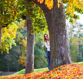 Belle jeune femme en parc d'automne se cachant derrière un arbre Photographie stock