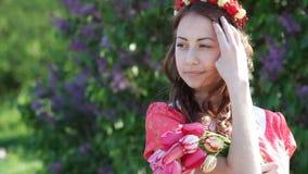 Belle jeune femme en parc de ressort avec une guirlande des fleurs banque de vidéos