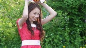Belle jeune femme en parc de ressort avec une guirlande des fleurs clips vidéos
