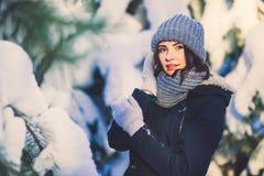 Belle jeune femme en parc le jour de chute de neige d'hiver Images stock