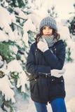 Belle jeune femme en parc le jour de chute de neige d'hiver Photos stock