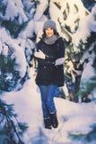 Belle jeune femme en parc le jour de chute de neige d'hiver Photographie stock