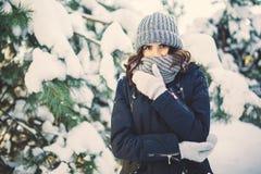 Belle jeune femme en parc le jour de chute de neige d'hiver Photographie stock libre de droits